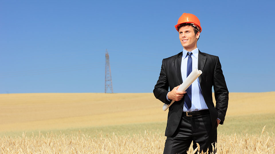 Man in field with plans and hardhat